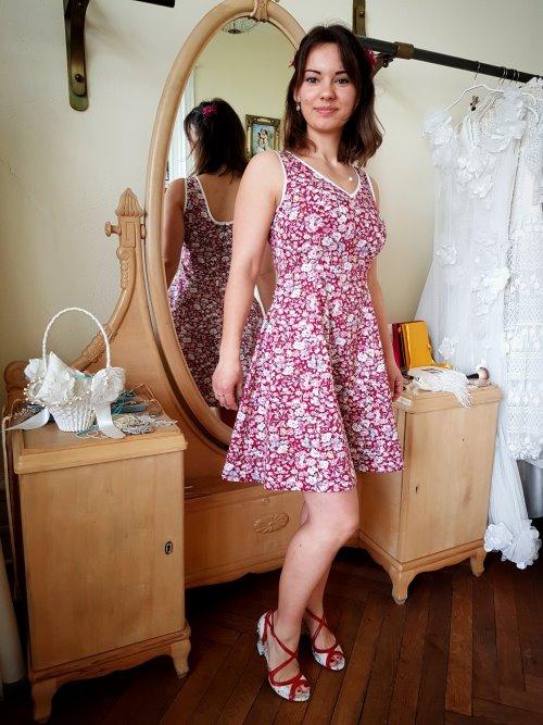 Frau im geblümten Sommerkleid vor einem Spiegel